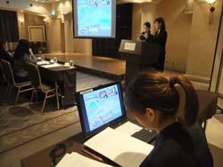 スクリーンに資料を映すためにパソコンで作業する学生