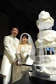 ケーキに入刀する新郎新婦役の学生