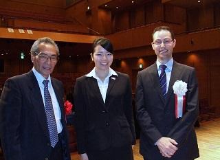 表彰式後に記念撮影(2)。左から、石塚理事長、冨岡さん、審査員毎日新聞社Mr. Aaron Baldwin