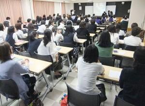 席について説明を聞く学校説明会の参加者たち