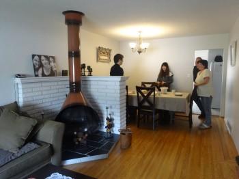 暖炉のある部屋の中でホストファミリーと談笑する学生