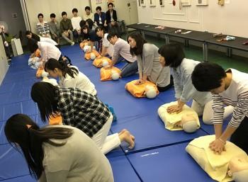 ダミー人形の胸に手を押し当てて心臓マッサージをする学生
