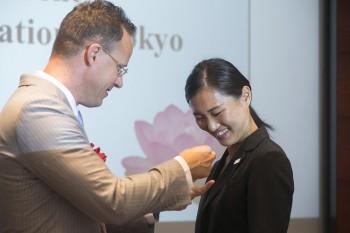 スペンス会長から2L 宮澤 彩さんへYSCJ会員Pinが授与される様子
