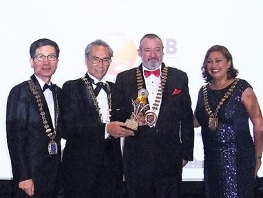 表彰式で国際会長からアジア地区最優秀賞トロフィーが送られる