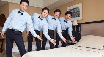 ホテルマンの恰好でベッドの前でポーズをとる男性