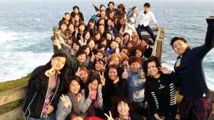 海を背景に記念写真を撮る学生たち