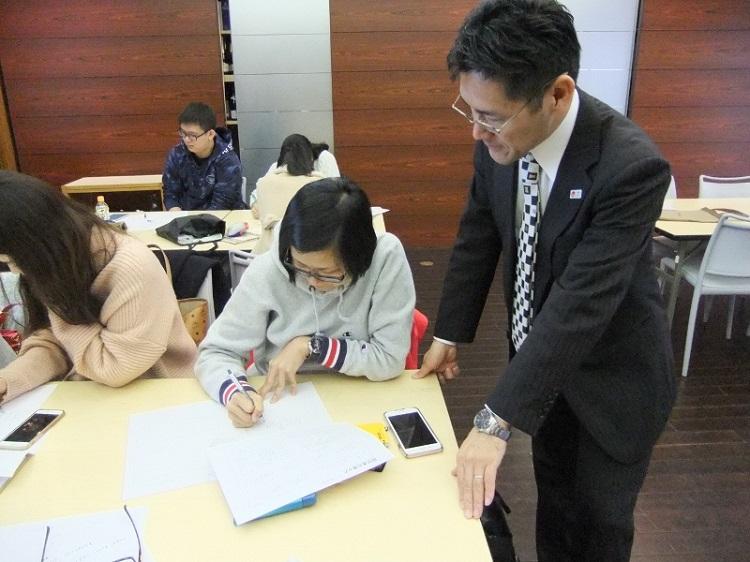 先生の指導を受けながら履歴書を書く留学生