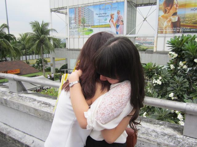 空港での別れで抱き合う学生ら