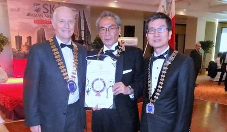 ヤングスコールクラブジャパンへの感謝として会長旗を受領する石塚校長