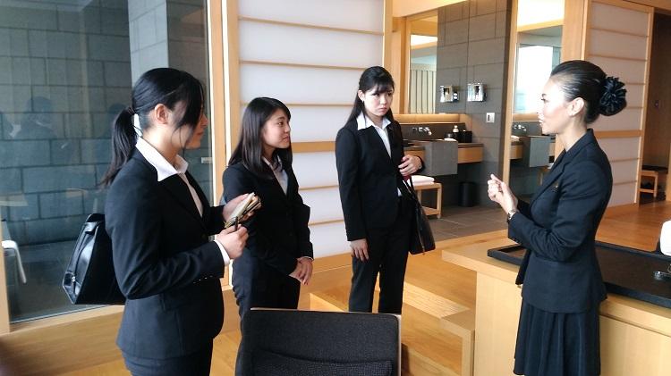 アマン東京の客室にて、説明を受けメモを取る学生