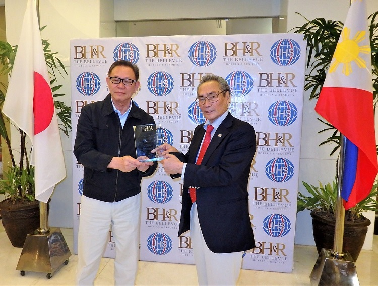 ベルビューホテル オーナー ジョニー・チャン氏(左)より「感謝の盾」を贈られる石塚校長