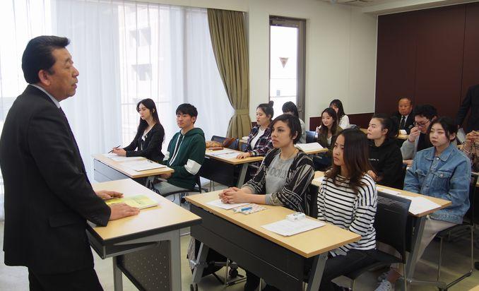 武内教育部長のお話を真剣に聞く留学生たち