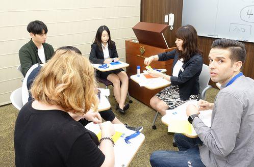 折りかたを説明する高野先生と真剣に聞く学生たち