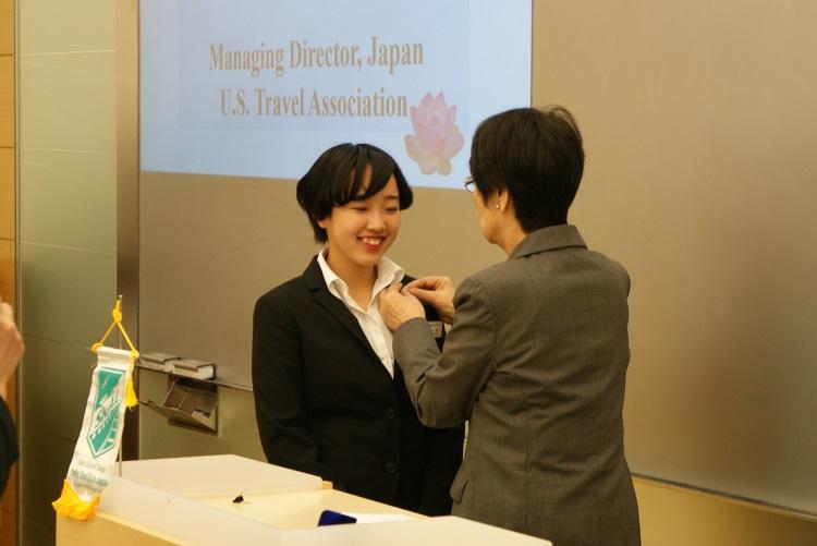 代表としてピンバッジを受ける柑谷実咲さん(左)と井上会長