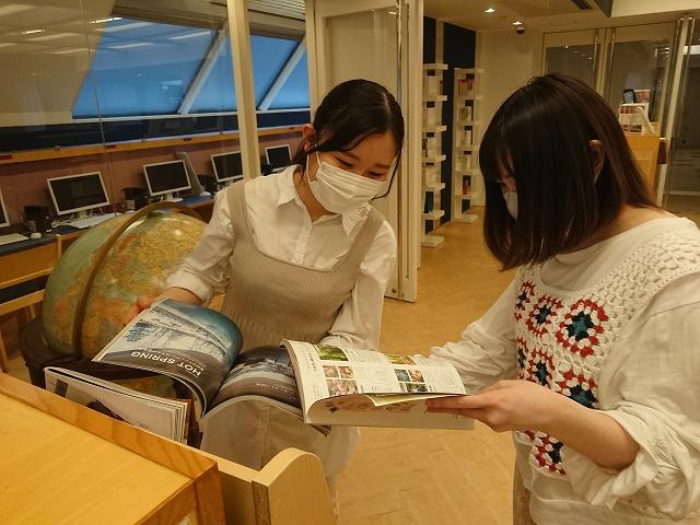 新しく設置したマガジンラックの業界誌から最新の情報を収集する学生