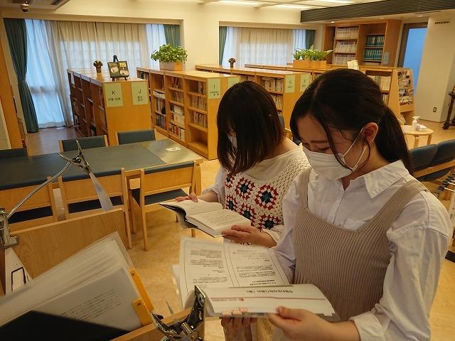 可動式ファイルラックの資料を参考にする学生